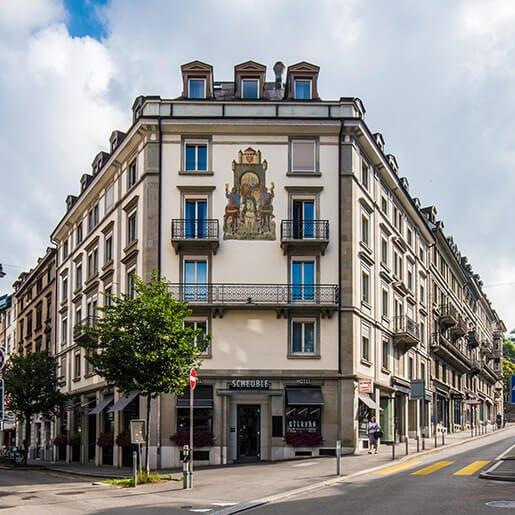 Unter Beste Hotels ist Hotel Scheuble die Nr. 1 gezeigt mit dem Vordereingang in schönem Wetter