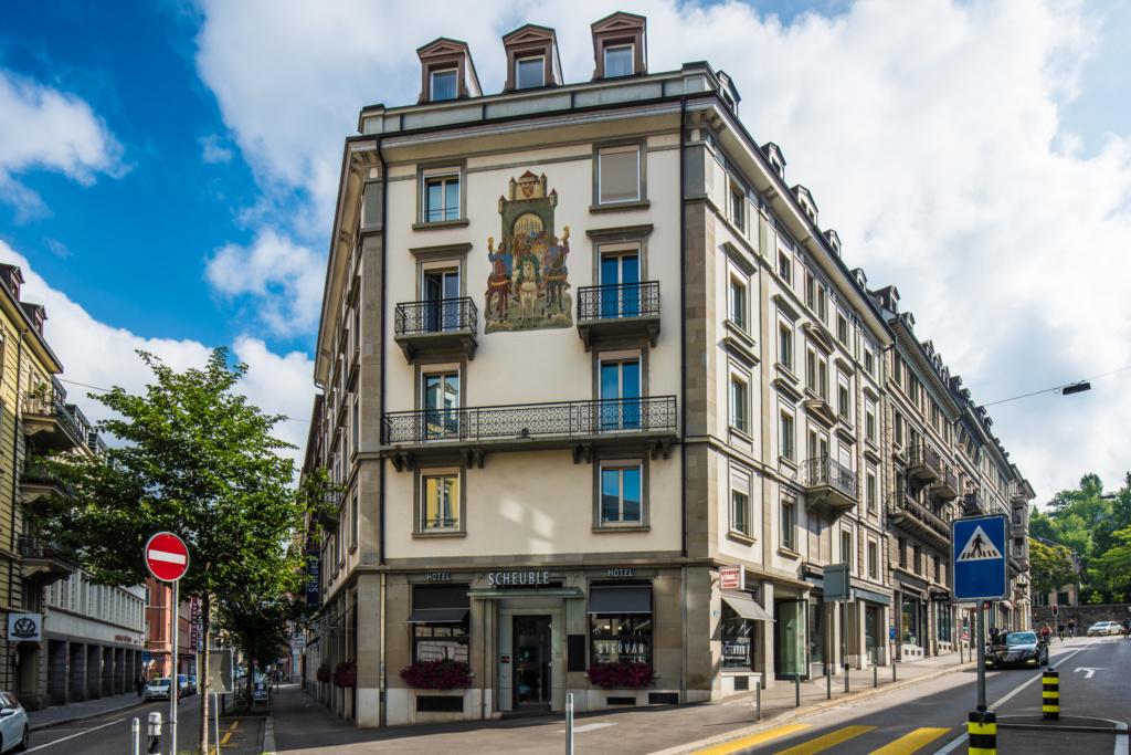 Eingang bei Hotel Scheuble, das die Nr. 1 bei günstige Hotels ist, mit Übernachtung und unter Hotel reservieren zu finden ist und ein Hotel mit Parkplatz ist mit einem grossen Angebot von einem einzigartigen Frühstück, Einzelzimmern, Doppelzimmern, Junior Suites und Twins. Das Beste Hotel buchen in Zürich.